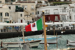 Italian flag on boat in sea port. Capri's sea port in the afternoon Stock Images