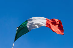 Italian Flag on a Clear Blue Sky Stock Images