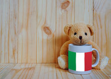 Italian flag on a coffee cup with teddy bear and wooden background. royalty free stock images