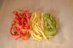 Italian flag Fettuccini. Three different colours of fettuccini ly next to each other on a light wooden surface to resemble the colours of the Italian flag Royalty Free Stock Photography