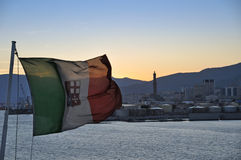Italian flag in Genova port. An Italian flag on a ferry leaving the port of Genova. The lighthouse Lanterna on the sunset background Stock Photography