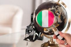 Italian flag on globe under magnifying Royalty Free Stock Image
