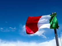 Italian Flag Green White and Red waving in a blue sky with clouds stock images