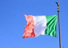 Italian flag. On iron stick blowing in the wind with blue sky behind royalty free stock images