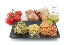 Italian flag made with pasta and ingredients on white background. Three color pasta representing italian flag with pesto, oil and tomato. Typical ingredients on Stock Image