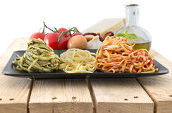Italian flag made with pasta and ingredients on white background. Three color pasta representing italian flag with pesto, oil and tomato. Typical ingredients on Stock Photos