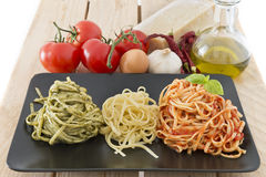 Italian flag made with pasta and ingredients on wood background. Three color pasta representing italian flag with pesto, oil and tomato. Typical ingredients on Royalty Free Stock Photo