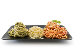 Italian flag made with pasta on white background. Three color pasta representing italian flag with pesto, oil and tomato on white background Stock Photos