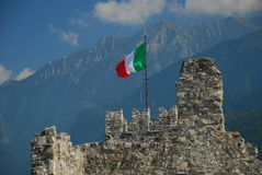 Italian flag on a medieval castle wall. Camonica valley, Italian flag on the Breno castle stone wall. Lombardy, Italy royalty free stock photography