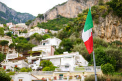 Italian flag over beautiful town of Positano at famous Amalfi coast Stock Images