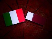 Italian flag with Qatari flag on a tree stump isolated Royalty Free Stock Image