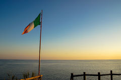 Italian flag at sunset. An Italian flag flaps in the breeze against a beautiful sunset Stock Photo