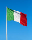 Italian flag. Tricolor flag flying in the blue sky royalty free stock photos