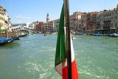 Italian flag and Venice Grand canal on background. Sunny summer day in Venice. Italian flag and Venice Grand canal on background Royalty Free Stock Photography