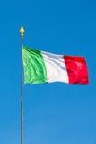 Italian flag waving into blue sky Stock Photo