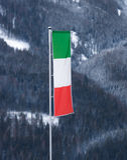 Italian flag waving on pole at ski resort Royalty Free Stock Image