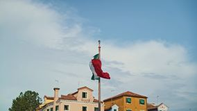 Italian flag waving in the wind with a blue sky and houses in the background. Real time shot stock footage