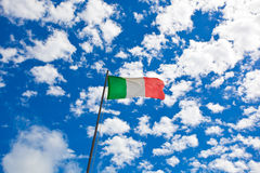 Italian flag waving in the wind over the blue sky Stock Photos