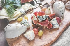 Italian Focaccia bread with cheese and a cheese plate with figs and Gorgonzola, brie, DorBlu and grapes. Royalty Free Stock Photo