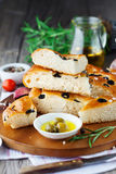 Italian focaccia bread. Freshly baked traditional Italian focaccia bread with rosemary and black olives on old wooden background, selective focus Stock Image