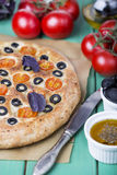 Italian focaccia with tomatoes, black olives and basil Royalty Free Stock Images
