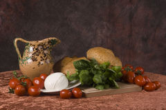 Italian food. Still life of fresh red tomatoes, Mozzarella cheese, basil and white bread with wooden board and jar stock image