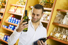 Italian food. Man in a supermarket comparing two wines Stock Photo