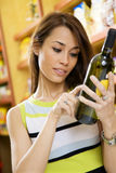 Italian food. Woman in a supermarket reading the label behind a bottle of wine Royalty Free Stock Photos