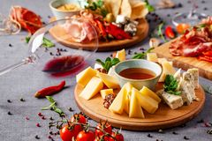 Italian food. Assortment of appetizers for a large company in a restaurant. Different types of smoked meat, sausages and cheeses. A glass of cool wine stock image