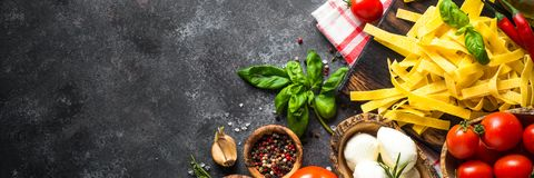 Spices and herbs over black stone table. Italian food background. Pasta, tomatoes, cheese, basil and olive oil on black stone table. TLong banner format stock photography