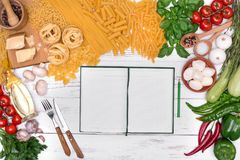 Italian food background, still life with italian ingredients with notebook on wooden table, top view Royalty Free Stock Photos
