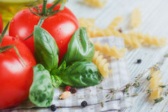 Italian food background, with tomatoes, basil, pasta, olive oil,. Peppercorns, chili pepper and thyme. Food concept Stock Photos