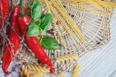 Italian food background, with tomatoes, basil, pasta, olive oil,. Peppercorns, chili pepper and thyme. Food concept Royalty Free Stock Images