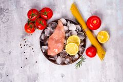 Pasta ingredients. Chicken breasts, tomatoes, spaghetti pasta, and lemon on the stone table. Italian food background. Uncooked Pasta, tomato, lemon and chicken Stock Image