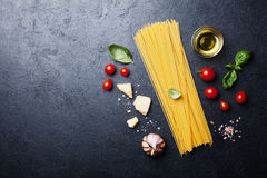 Italian food background with uncooked spaghetti, tomato, basil leaves, cheese, garlic and olive oil for cooking pasta stock image