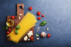 Italian food background with uncooked spaghetti, tomato, basil leaves, cheese, garlic and olive oil for cooking pasta. Royalty Free Stock Image