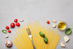 Italian food background with uncooked spaghetti, tomato, basil leaves, cheese, garlic and olive oil for cooking on stone table Stock Images