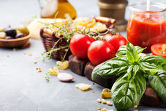 Italian food background with vine tomatoes, basil, spaghetti, olives Ingredients on stone table Copy space Royalty Free Stock Photos