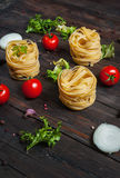 Italian food cooking ingredients. Pasta, tomatoes, onion on dark wooden background Stock Photos