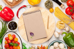 Italian food cooking ingredients. Pasta, vegetables, spices. Top view with notepad for copy space Stock Image