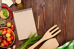 Italian food cooking ingredients. Pasta, vegetables, spices. Top view with notepad for copy space Royalty Free Stock Images