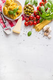 Italian food cuisine and ingredients on white concrete table. Spaghetti Tagliatelle olives olive oil tomatoes parmesan cheese. Italian food cuisine and stock image
