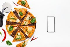 Italian food delivery. Pizza slices and smartphone with blank screen. On white background, top view stock images