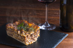 Italian food fresh hot steaming lasagna pasta served on wooden table and slate plate Stock Photography