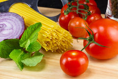 Italian food ingredients. Pasta, onion, tomato and herbs Royalty Free Stock Photos