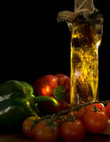 Italian food ingredients. A still life of ingredients for Italian food. Peppers and tomatoes are illuminated by the sun which is shining through a bottle of stock photo