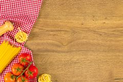 Italian food and raw ingredients on wooden background. Top view. Italian food ingredients and checkered napkin on wooden table. Top view with space for your text Royalty Free Stock Photography