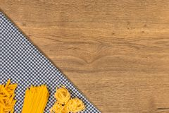 Italian food and raw ingredients on wooden background. Top view. Italian food ingredients and checkered napkin on wooden table. Top view with space for your text Royalty Free Stock Photo