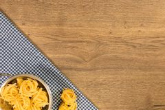 Italian food and raw ingredients on wooden background. Top view. Italian food ingredients and checkered napkin on wooden table. Top view with space for your text Stock Photo