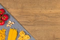 Italian food and raw ingredients on wooden background. Top view. Italian food ingredients and checkered napkin on wooden table. Top view with space for your text Stock Photos